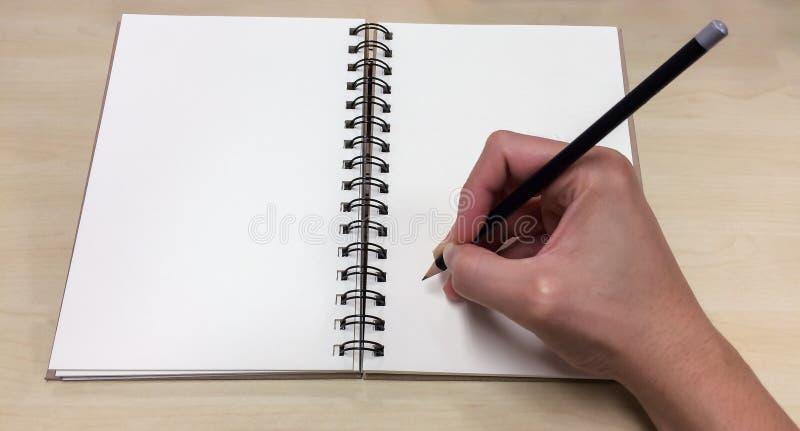As páginas vazias Open registram com a mão masculina asiática que mantém o lápis preto pronto para escrever para baixo fotos de stock