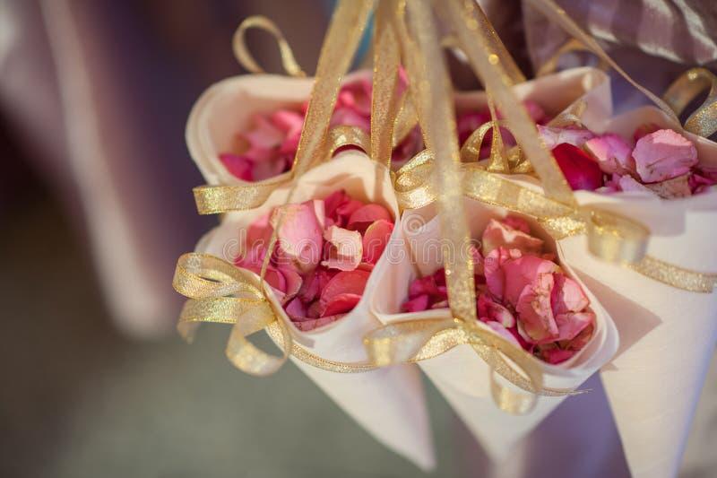 As pétalas de rosas envolveram no papel para decoram na cerimônia de casamento imagens de stock
