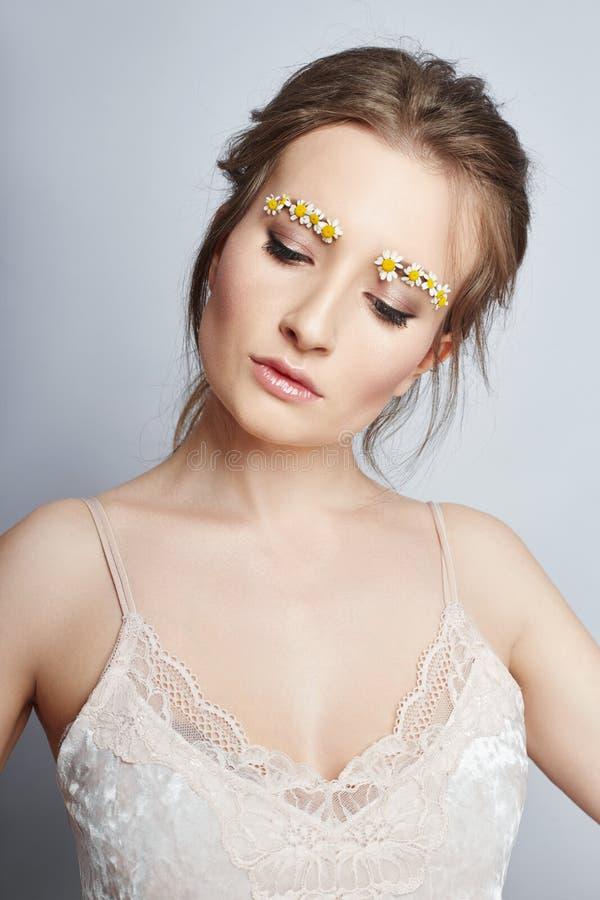 As pétalas na menina da cara, cosméticos da flor da mulher para hidratar a pele da cara, reduzem enrugamentos, limpam a pele saud imagem de stock