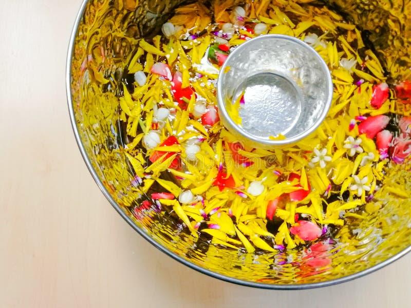 As pétalas pequenas da bacia e da flor flutuam na água na grande bacia, no grupo para adultos molhando no ano novo tailandês o foto de stock royalty free