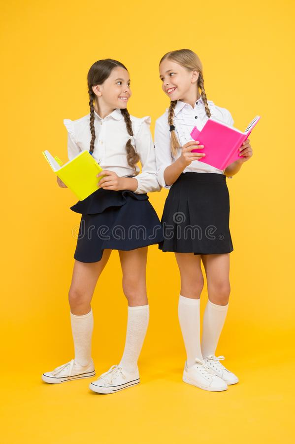 As the Page Turns. little girls in school uniform. reading story. childrens literature. kids learning grammar. back to. School. dictionary notebook. Get stock photos