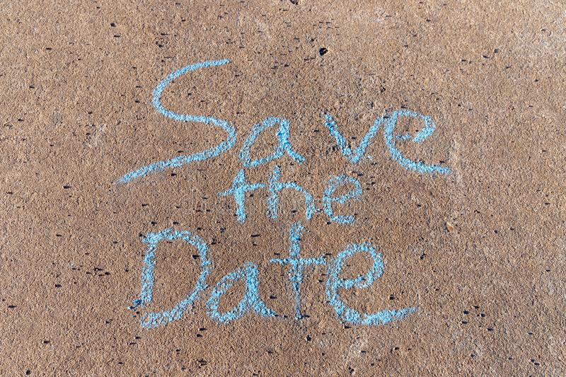 As palavras salvar a data escrita com giz do passeio no fundo concreto cinzento foto de stock