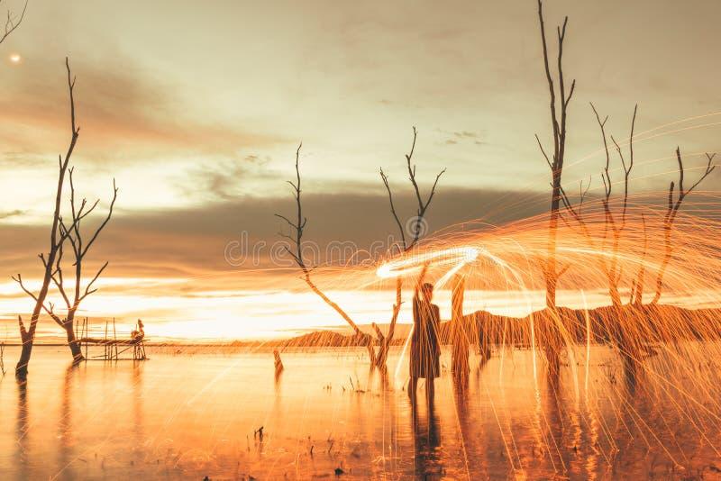 As palhas de aço do balanço do homem criam como o fogo de artifício e o por do sol de surpresa foto de stock royalty free