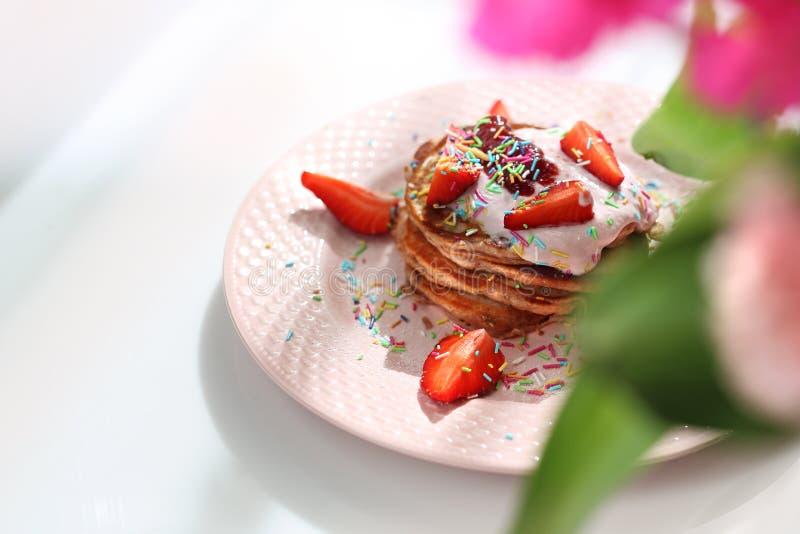 As panquecas cor-de-rosa com morangos, requeijão e açúcar colorido polvilham foto de stock
