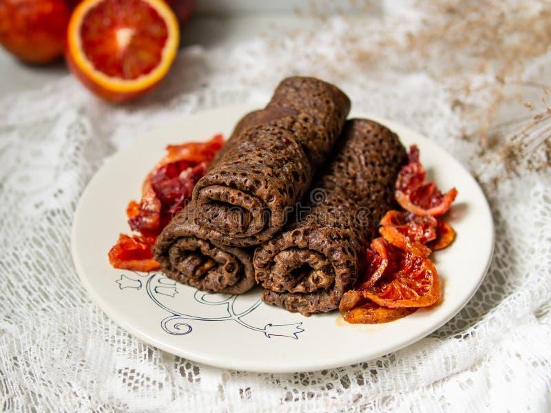 As panquecas finas do chocolate rolaram em um tubo com molho das laranjas pigmentadas em uma placa branca Pilha de crepes, blin d imagens de stock