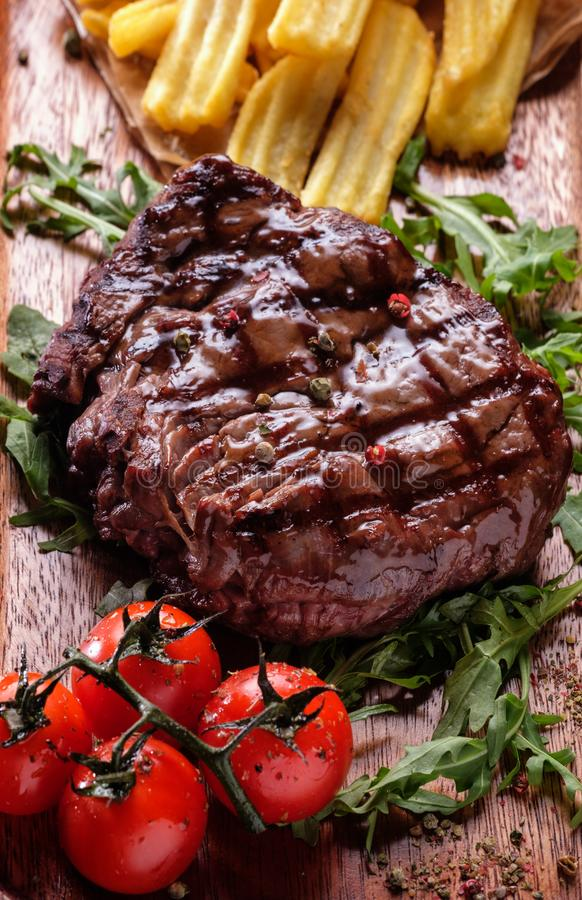 As parcelas suculentas de bife de vaca grelhado serviram com tomates e imagem de stock