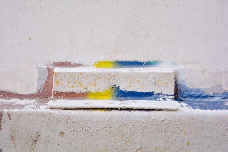 As paredes velhas são pintadas com pintura branca, azul, vermelha e amarela fotos de stock royalty free