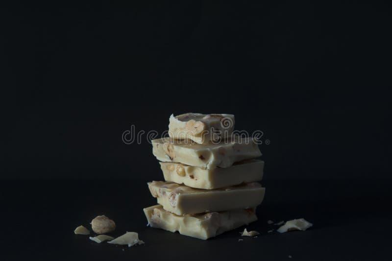 As partes aproximadamente desbastadas do chocolate branco com nozes ajustaram-se sobre se com fundo escuro imagens de stock