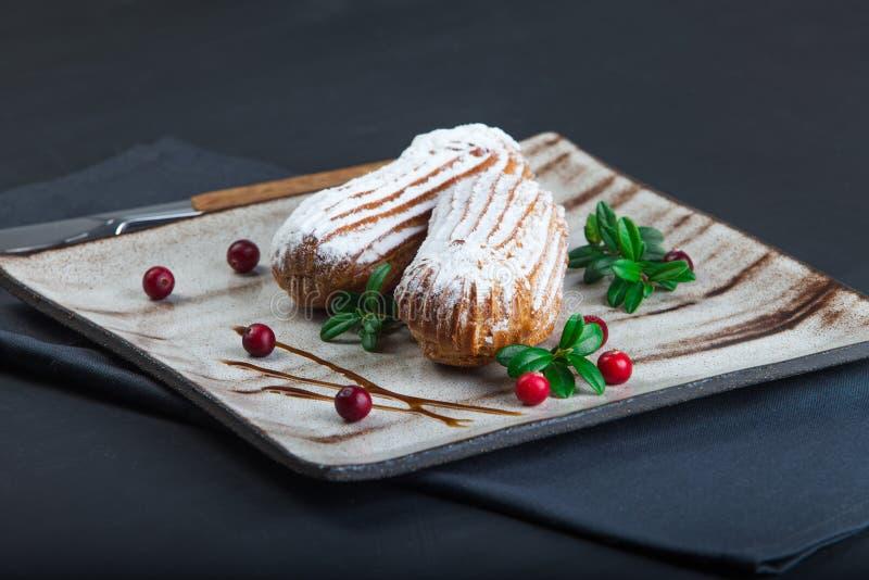 As pastelarias de creme dos choux dos eclairs serviram com arandos frescos em uma placa cerâmica feito a mão Queques de Profitero fotografia de stock