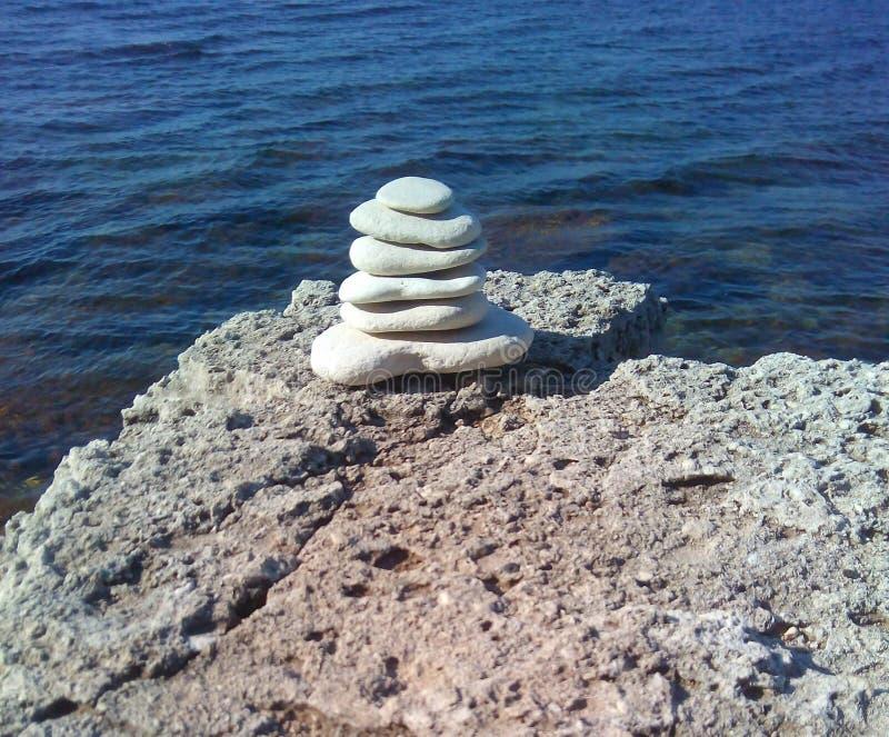 As pedras bonitas equilibram em um fundo da rocha da pedra do mar fotos de stock royalty free