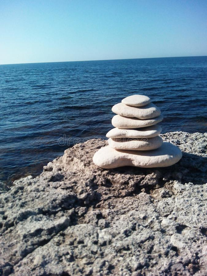 As pedras bonitas equilibram em um fundo da rocha da pedra do mar foto de stock royalty free