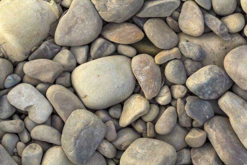 As pedras cinzentas grandes e pequenas do rio fecham-se acima do fundo foto de stock