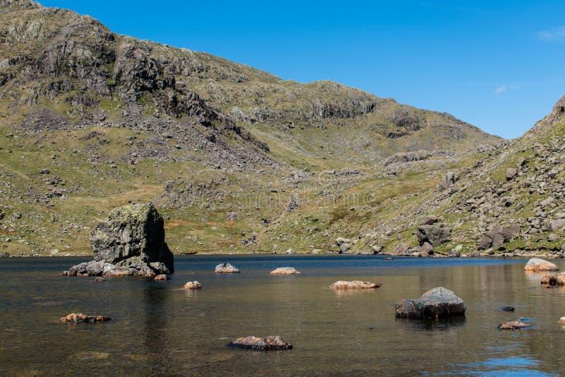 As pedras dispersaram em um corpo de água raso no distrito do lago, Reino Unido fotos de stock royalty free