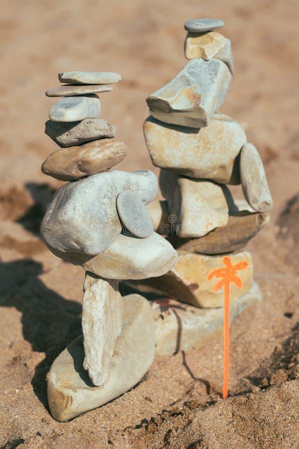 As pedras encontram-se nas pedras shui do feng na praia Criando um equilíbrio na areia fotografia de stock royalty free
