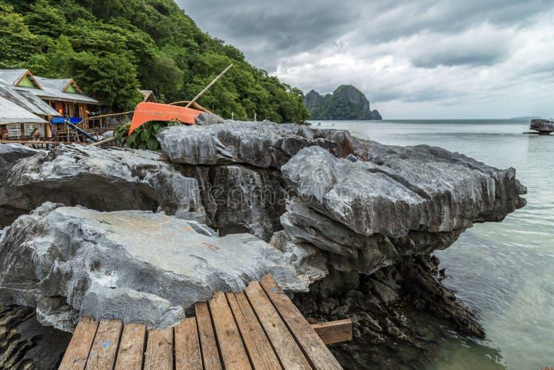 As pedras rochosas estão estando no raso do mar no dia nebuloso imagem de stock