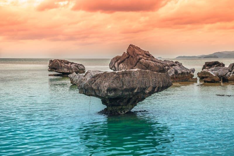 As pedras rochosas estão estando no raso do mar no tempo do por do sol foto de stock royalty free
