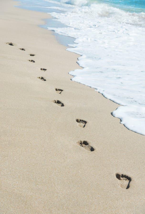 As pegadas na areia da praia do mar com onda espumam fotos de stock