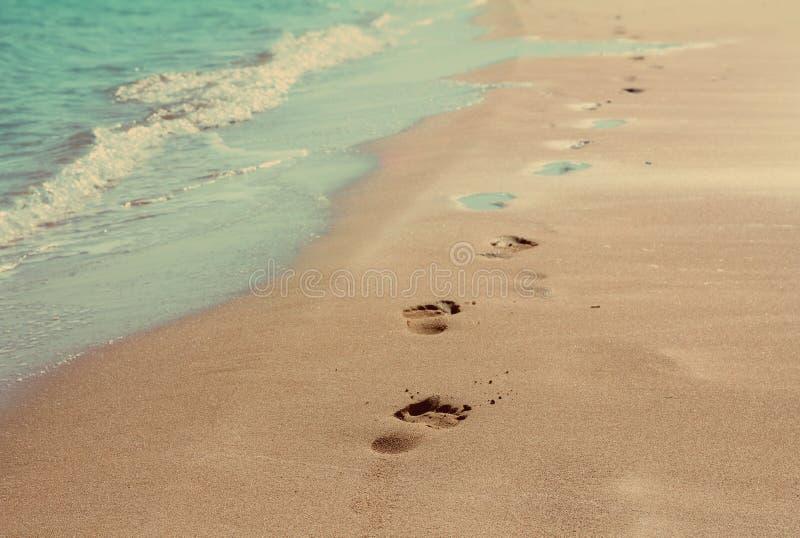 As pegadas na areia encalham - o estilo retro do vintage imagem de stock