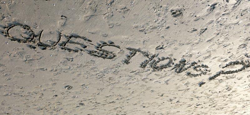 As PERGUNTAS da palavra com o ponto de interrogação escrito na areia podem ser uso imagem de stock