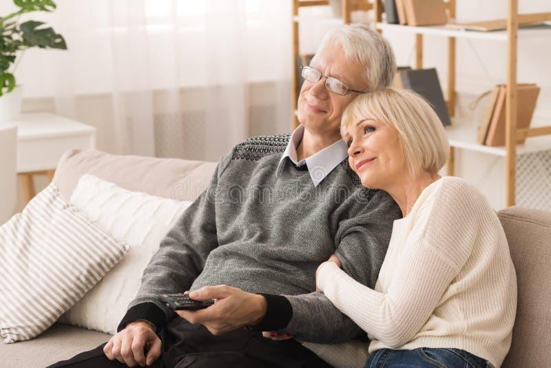 As pessoas idosas de amor acoplam a tevê de observação, descansando em casa foto de stock royalty free