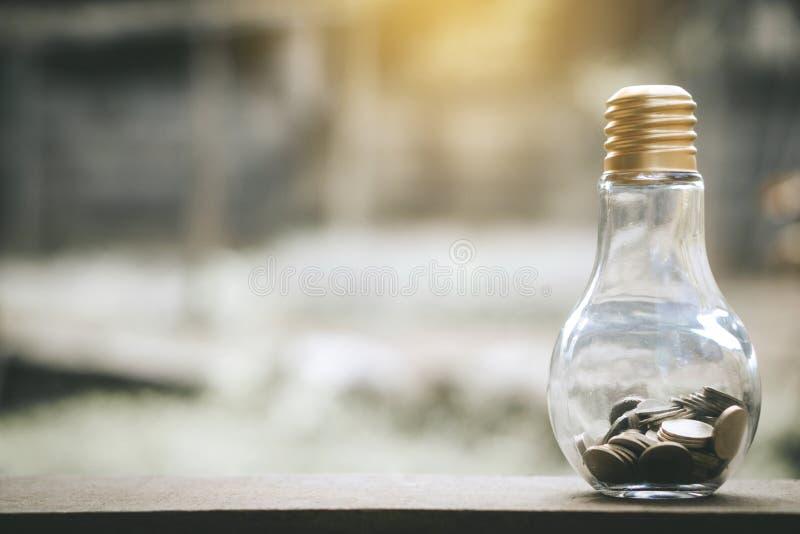 As pilhas da moeda no banco do vidro de garrafa para intensificam o negócio crescente para lucrar e o conceito de salvamento foto de stock royalty free