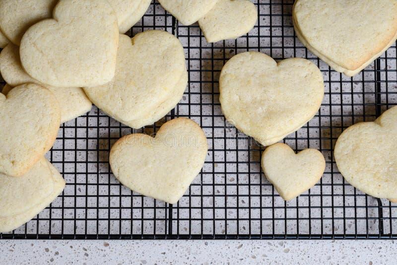 As pilhas de coração deram forma a cookies de açúcar em uma cremalheira refrigerando do fio preto, contador de cozinha do granito fotos de stock royalty free