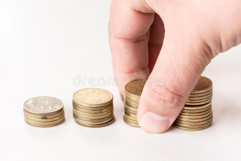 As pilhas do metal inventam acima do fundo branco e da mão que guardam a pilha das moedas imagem de stock