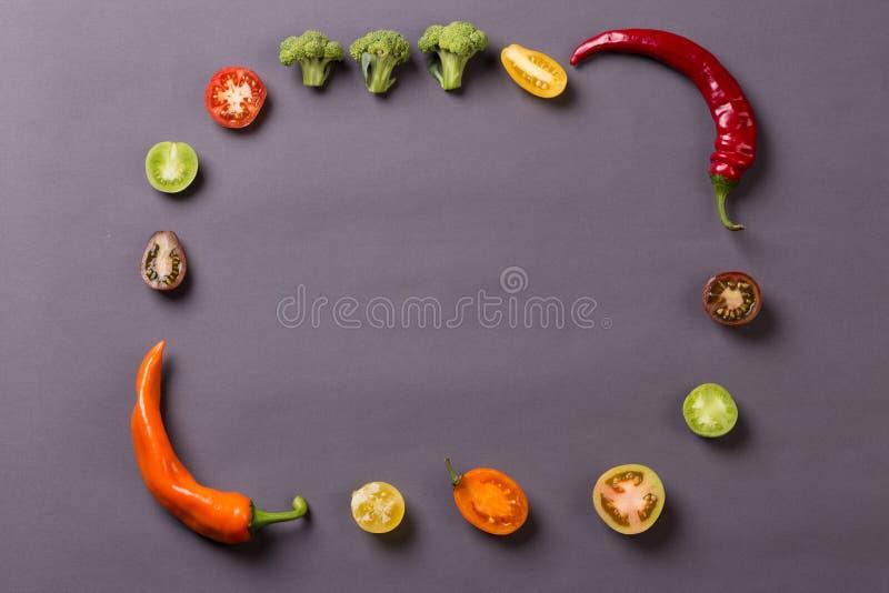 As pimentas com tomates e brócolis no fundo cinzento compõem o quadro foto de stock royalty free