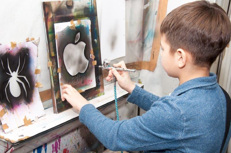 As pinturas do adolescente do menino com um aerógrafo coloriram brilhantemente imagens em um estúdio artístico - Rússia, Moscou - fotos de stock royalty free