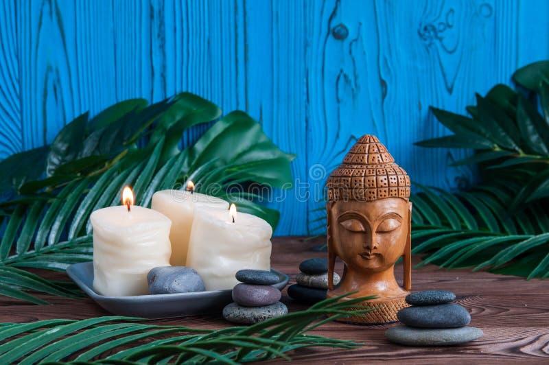 As pirâmides de pedras cinzentas do zen com velas, verde saem no fundo de madeira Conceito da harmonia, do equilíbrio e da medita fotografia de stock