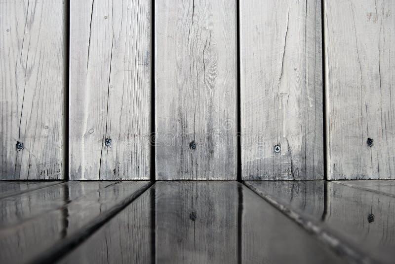 As placas de madeira da parede refletiram na água no assoalho foto de stock