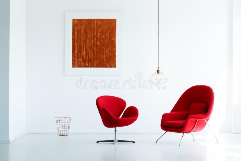 As poltronas vermelhas ajustaram-se em uma parede branca com uma pintura e na lâmpada na imagem de stock royalty free