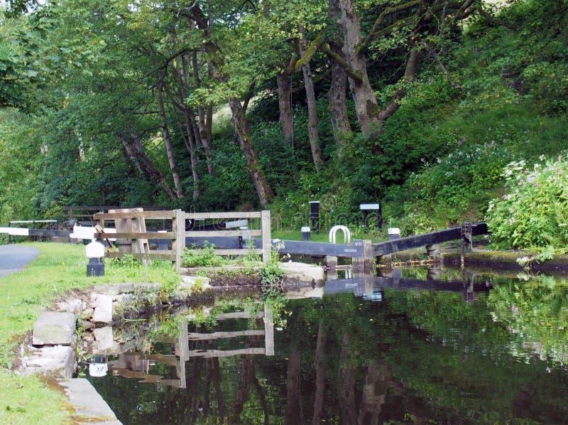 As porta de eclusa de madeira velhas com árvores e as flores refletidas na água com cargos e cercas da amarração no canal do roch fotografia de stock