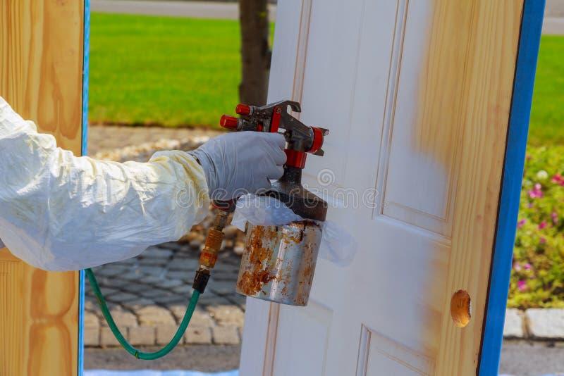 As portas de madeira da pintura mestra pintam a porta com um pulverizador fotografia de stock royalty free