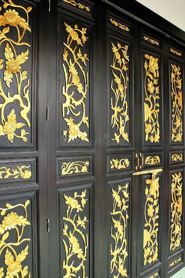 As portas de madeira são testes padrões dourados pintados na porta fotografia de stock