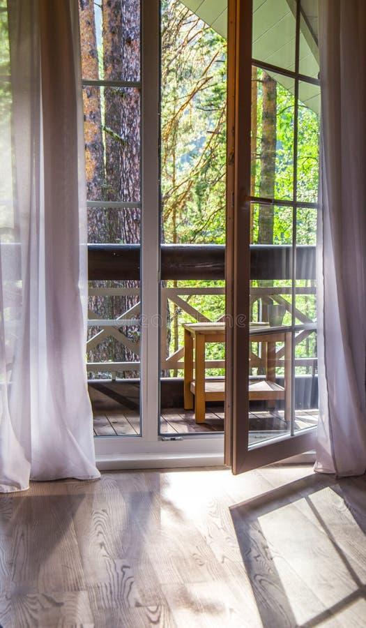 As portas francesas abrem em um balcão com uma vista de árvores verdes frondosas nave Relaxe o conceito vocations fotos de stock