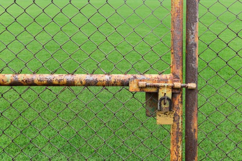 As portas oxidaram uso fechado da cerca do ferro não o gramado imagens de stock