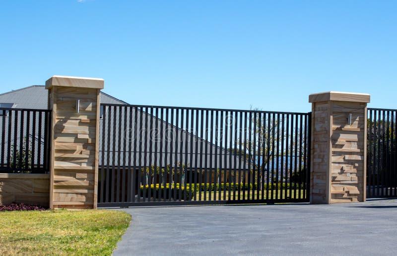 As portas pretas da entrada da entrada de automóveis do metal ajustaram-se na cerca do tijolo do arenito com jardim residencial imagem de stock