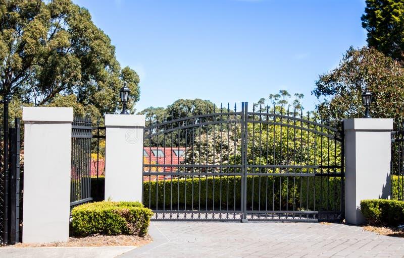 As portas pretas da entrada da entrada de automóveis do metal ajustaram-se na cerca do tijolo com as árvores do jardim no fundo fotografia de stock royalty free