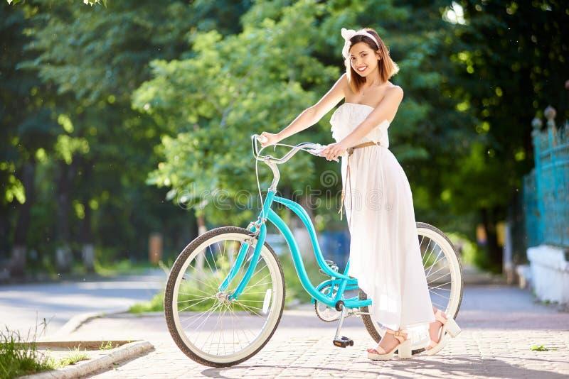 As poses modelo com vintage azul bicycle em uma rua da cidade foto de stock