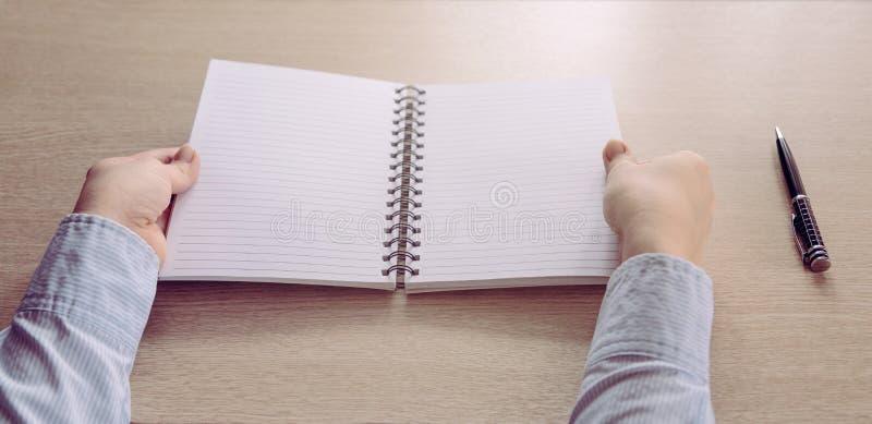 As posses fêmeas das mãos abriram o caderno vazio fotografia de stock royalty free