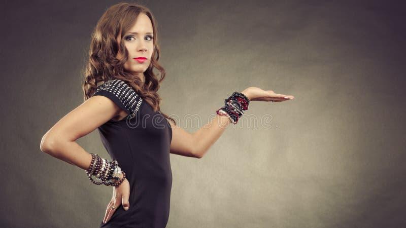 As posses vestindo dos braceletes da mulher elegante abrem a mão fotografia de stock
