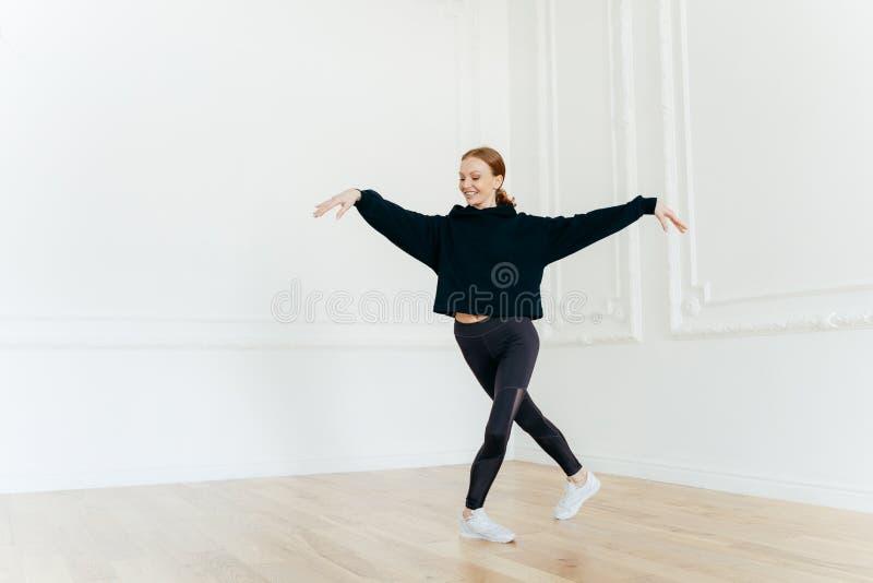 As práticas fêmeas profissionais da bailarina dançam no salão, esticam as mãos, suportes com pés cruzados, têm o sorriso delicado fotografia de stock royalty free