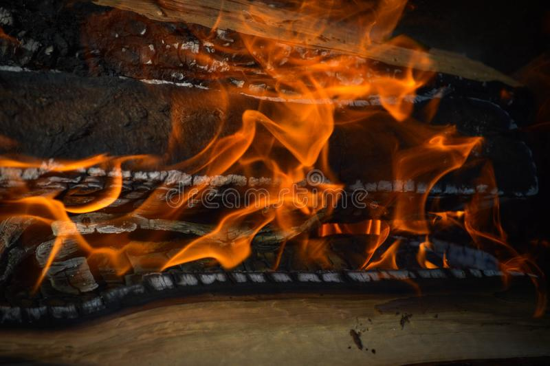 As pranchas carbonizadas quentes ardentes de madeira da madeira entram um fogo com as línguas do fogo e do fumo Textura, fundo imagem de stock