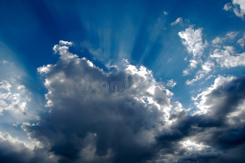 As raias de luz quebram através das nuvens de tempestade da tarde fotografia de stock royalty free