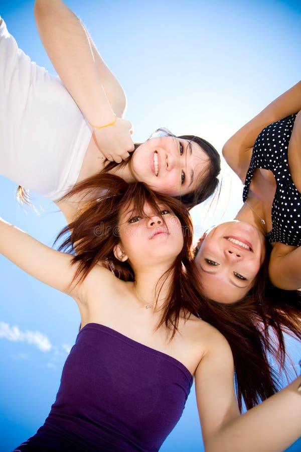 As raparigas recolhem ao redor sob o céu ensolarado brilhante imagem de stock