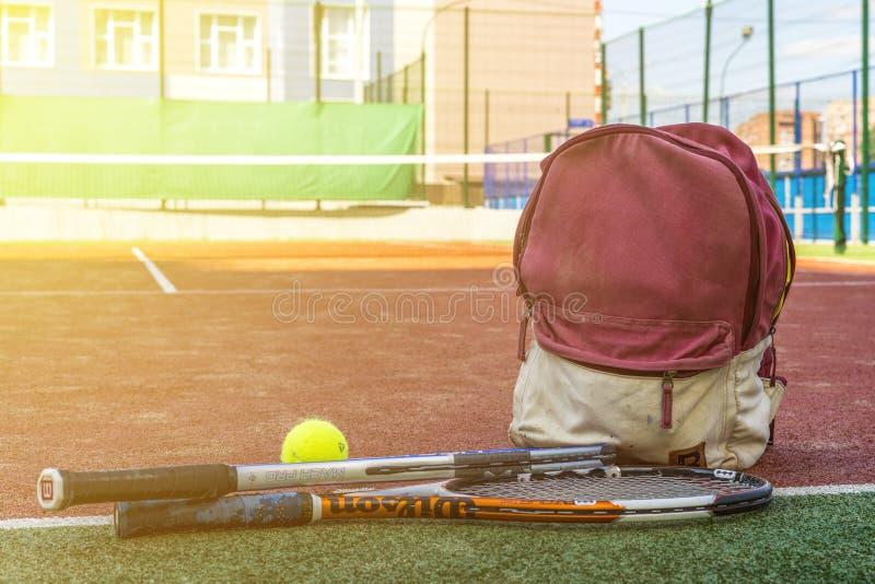 As raquetes de tênis com uma bola perto do esporte ensacam com equipamento na corte no dia de verão foto de stock