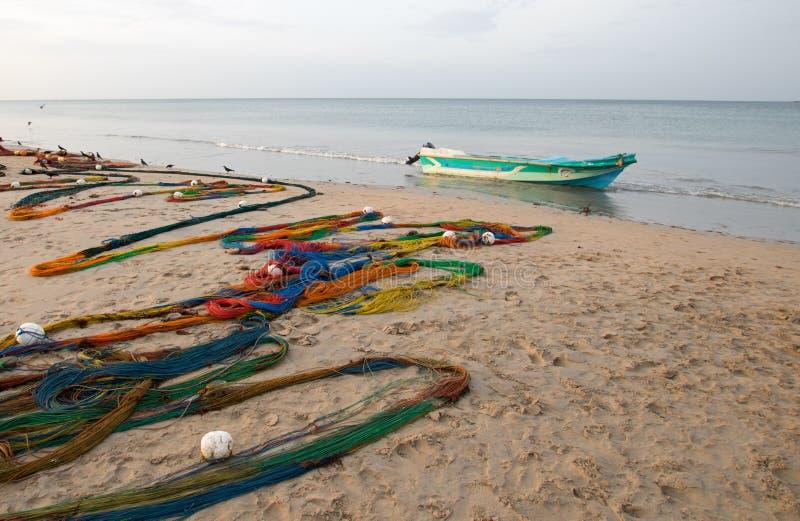 as redes de pesca Multi-coloridas que secam no sol ao lado do barco de pesca pequeno em Nilaveli encalham em Trincomalee Sri Lank imagem de stock