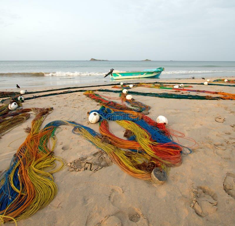 as redes de pesca Multi-coloridas que secam no sol ao lado do barco de pesca pequeno em Nilaveli encalham em Trincomalee Sri Lank foto de stock