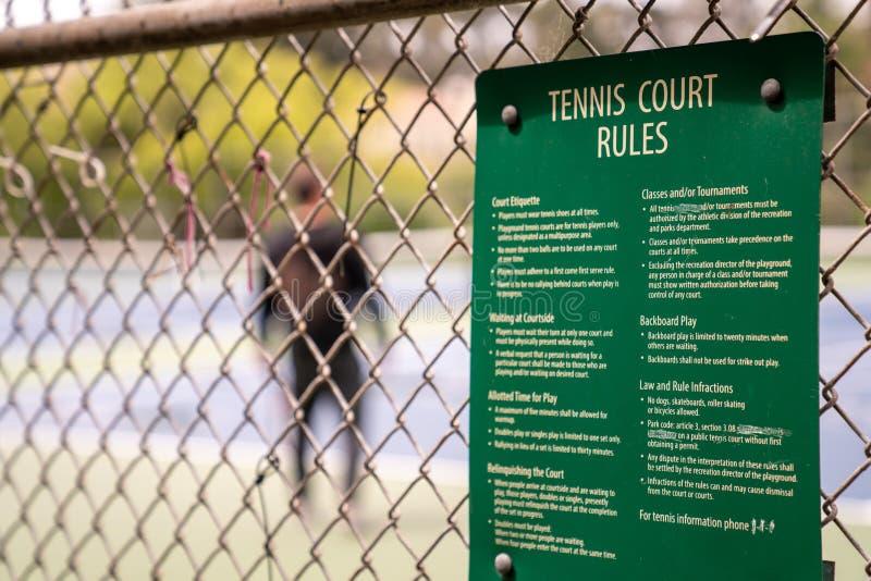 As regras do campo de tênis afixaram fora de um campo de tênis da comunidade com o homem que joga no fundo imagem de stock
